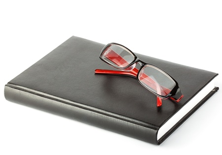 Study. Book with eyeglass on the white background photo