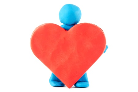 Plasticine man with plasticine heart on the white background photo