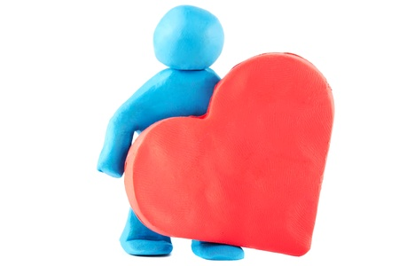 Plasticine man with plasticine heart on the white background Stock Photo