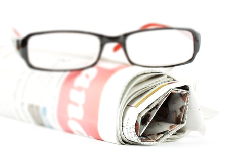 commentary: Extreme Closeup Reading glasses with newspaper Stock Photo