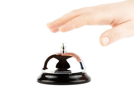 campanas: Haciendo sonar una campana para el servicio con la mano en el fondo blanco Foto de archivo