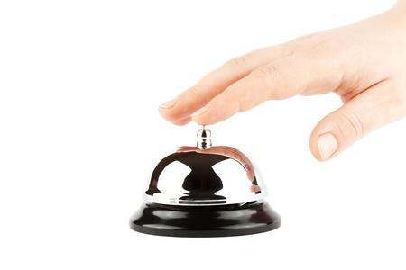 Ringer en klocka för service med handen på den vita bakgrunden