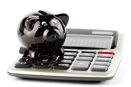 Calculator and black closeup piggy bank on white background photo
