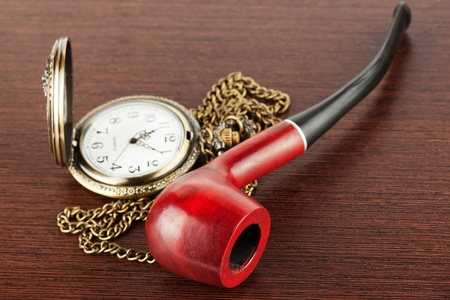 Pocket watch with a lid and smoking tube on a wooden table photo