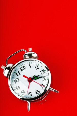 Closeup Alarm clock on the red background photo