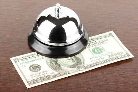 front desk: Service Bell with money on the wooden desk Stock Photo