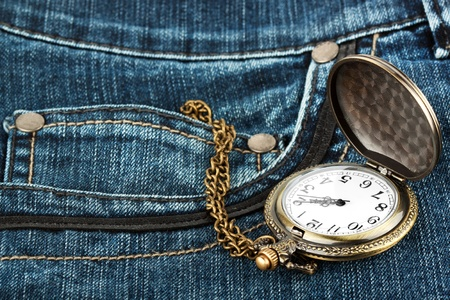 Closeup pocket watch in pocket of jeans photo