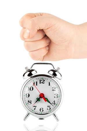 Alarm clock and a fist on the white background photo