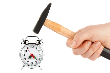 Time management - Hand holding a hammer about to hit the alarm clock photo