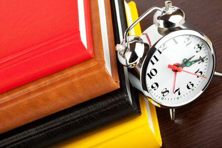 Alarm clock and colourful books extreme closeup photo