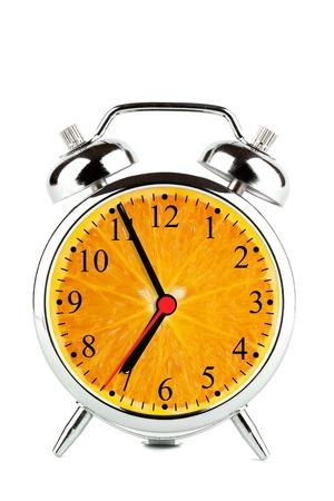 Alarm Clock made of orange fruit on the white background photo
