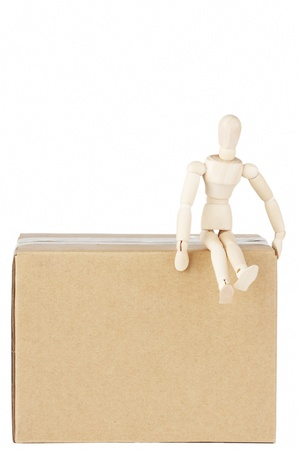 Wooden mannequin sitting on top the box on the white background photo