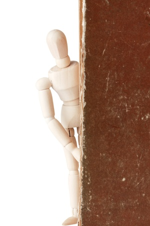 Wooden dummy and old book on a white background photo
