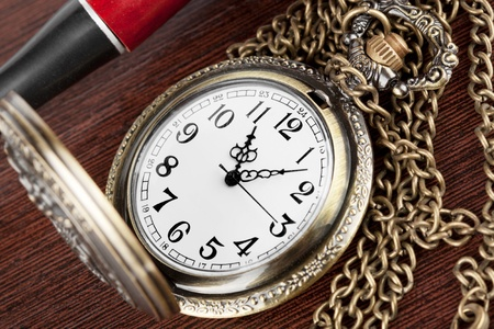 Pocket watch with a lid on a wooden table photo