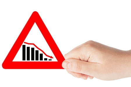 Downward trend concept. Chart on a Triangular red road signs with hand on a white background photo