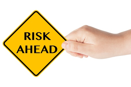Risk ahead sign showing business concept with hand on the white background photo