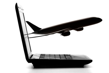 Laptop computer with airliner flying out from screen on a white background photo