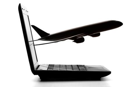 reservacion: Ordenador port�til con el avi�n volando en la pantalla sobre un fondo blanco Foto de archivo