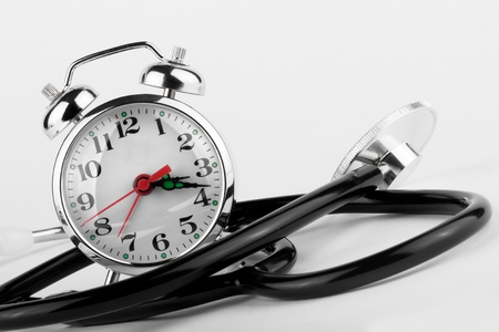 Health Time Medical concept. Alarm clock with stethoscope on a white background photo