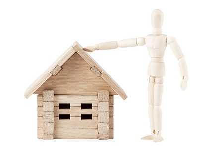 Dummy with wooden home on a white background photo