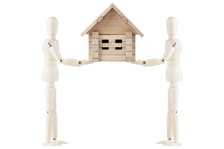 Two dummy hold wooden home in hand on a white background photo