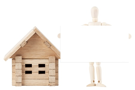 Dummy with wooden home on a white background with blank sign for your text photo