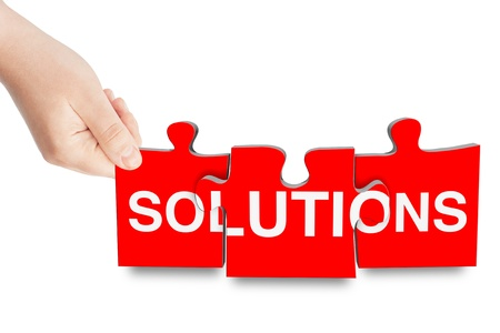 Solutions sign puzzle in hand on a white background