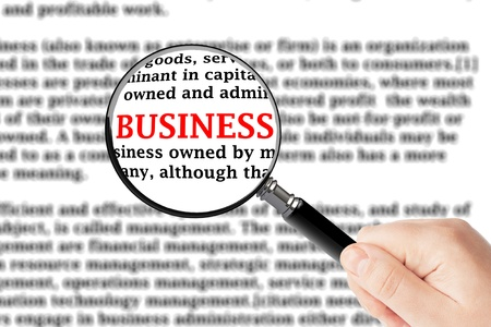 Magnifying glass in hand and business sign photo