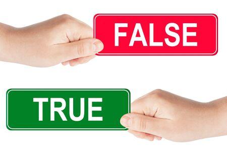 falso: El tráfico de verdadero y falso signo en la mano en el fondo blanco Foto de archivo