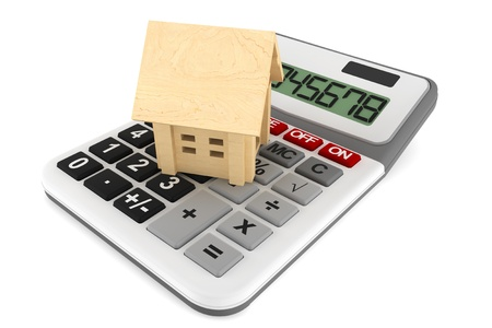 home prices: Wooden House with Calculatoron a white background  Stock Photo