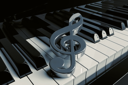 musical theater: Silver treble clef is on extreme closeup piano keys