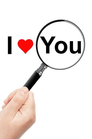 Womans hand, holding classic styled magnifying glass, with I Love You sign photo