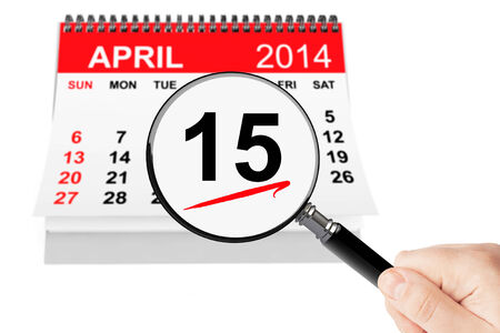 Tax Day Concept. 15 april 2014 calendar with magnifier on a white background photo