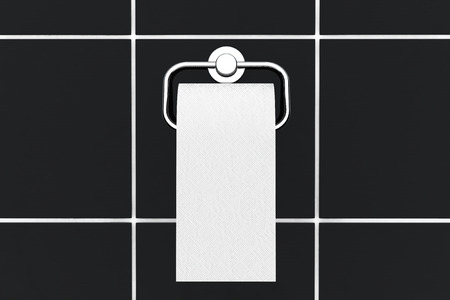 Toilet paper on chrome holder on a black tiles background photo