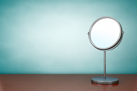 Foto do estilo velho. Espelho de maquiagem Chrome em cima da mesa