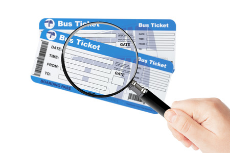 Bus boarding pass tickets with magnifier glass in hand on a white background photo
