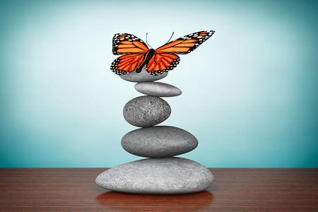 healing: Old Style Photo. Balanced stones with butterfly on the table