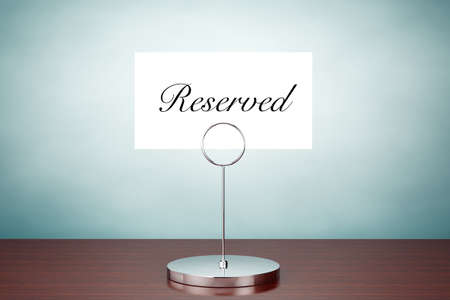 sign holder: Old Style Photo. Note Paper Card Holder with Reserved Sign on the table Stock Photo