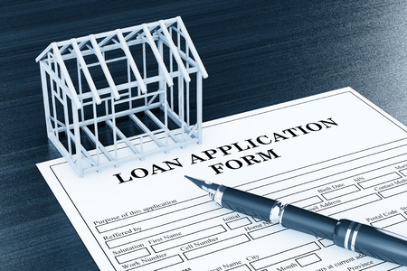 endorsing: Loan Application Form with House Frame and pen on the table