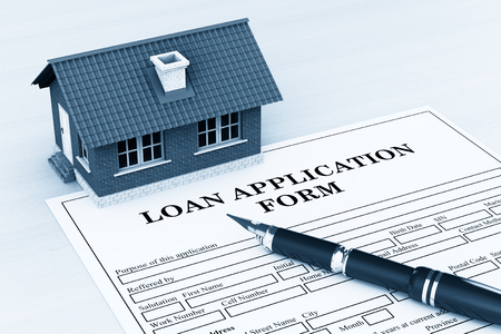 endorsing: Loan Application Form with House and pen on the table