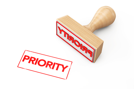 Wooden Rubber Stamp with Priority Sign on a white background Stock Photo