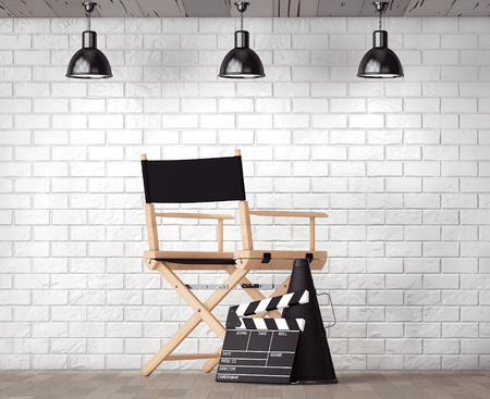 antique chair: Director Chair, Movie Clapper and Megaphone in front of Brick Wall with Blank Frame extreme closeup Stock Photo