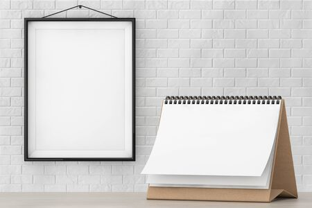 Blank Paper Desk Spiral Calendar in front of Brick Wall with Blank Frame extreme closeup Stock Photo