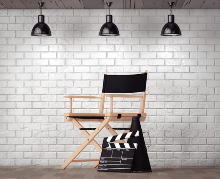 Director Chair, Movie Clapper and Megaphone in front of Brick Wall with Blank Frame extreme closeup Stockfoto