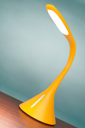 sensor: Concept of Yellow Led Sensor Desk Lamp on a wooden table. 3d Rendering