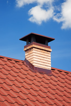Modern Ceramic Tile Roof with Chimney against the Sky extreme closeup.