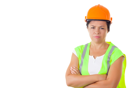 Serious Attractive Woman Worker in Safety Jacket and Yellow Helmet on a white background Stock Photo