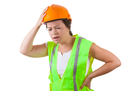 Attractive Woman Worker in Safety Jacket and Yellow Helmet Suffers from Backache on a white background Stock Photo