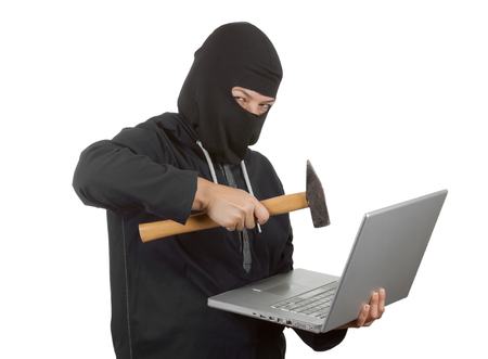 Criminal Woman Hacker Wearing Hood On in Black Clothes and Balaclava Destroy  Laptop with Hammer on a white background