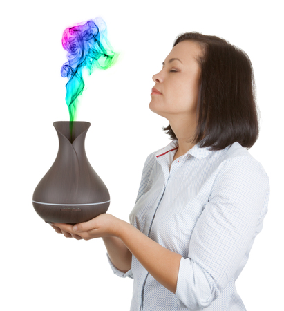 Aromatherapy Concept. Beautiful Woman Smelling Color Steam from Wooden Electric Ultrasonic Essential Oil Aroma Diffuser and Humidifier on a white background